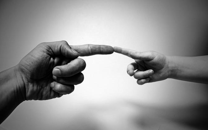 Рука ребенка и взрослого человека