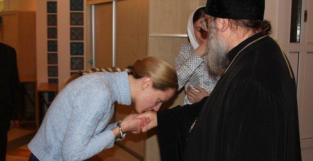 Верующий целует руку священнику
