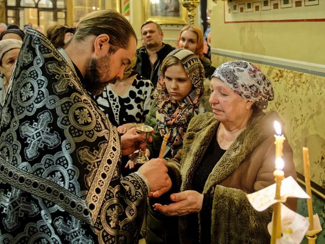 Священник помазывает руки верующих