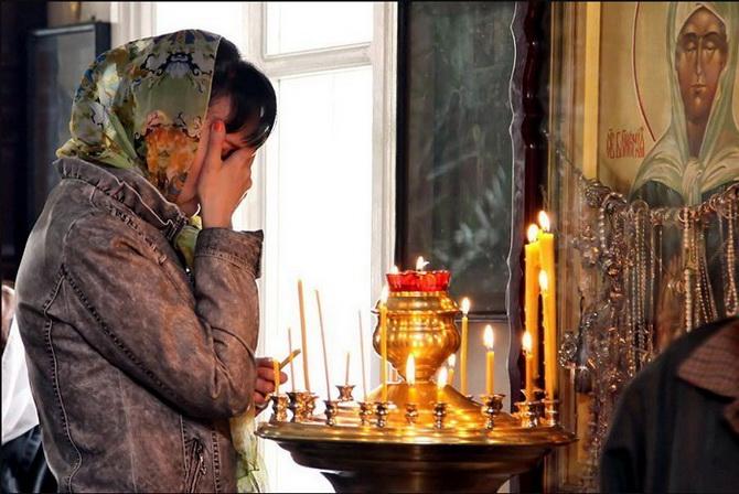 Женщина молится в храме
