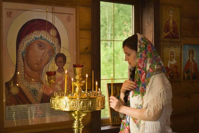 Девушка молится в храме