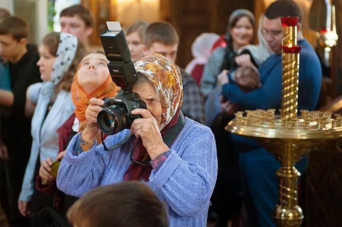 Бабушка делающая фото в храме