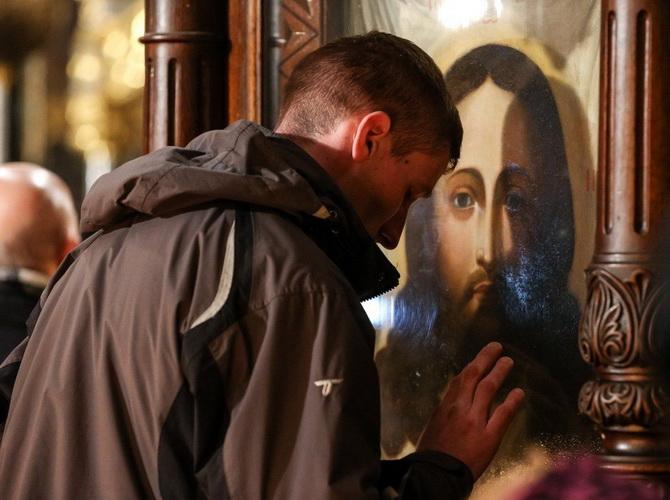 Человек молится перед иконой